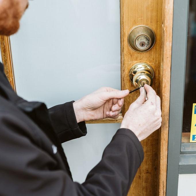 locksmith unlocking home front door with locksmith tools